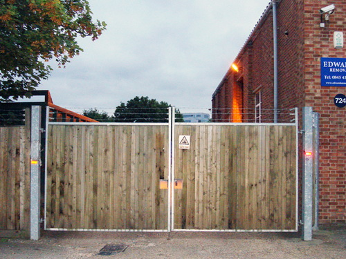 Iron framed wooden high security double gates.  3 levels of barbed wire for total security.